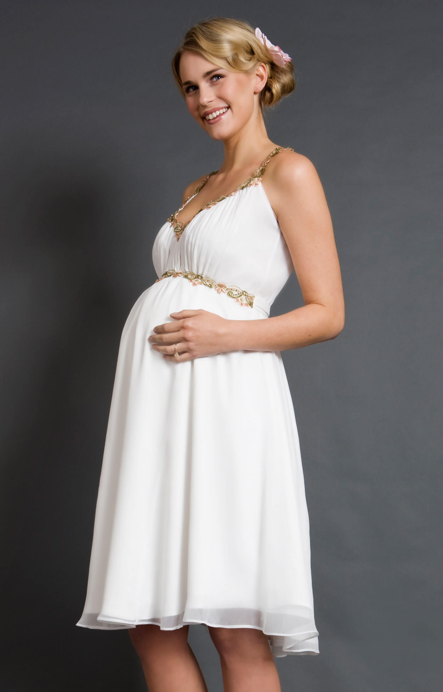A vision in mist gray chiffon; our embellished Grecian maternity gown is a truly romantic choice for your glamorous evening occasion. Exquisite hand beading at the shoulders and empire waist catch the light and shimmer as you move, giving a subtle shine to the style.